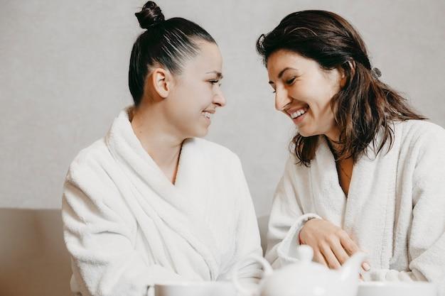 Zijaanzicht portret van twee mooie jonge blanke vrouw plezier lachen zittend in een wellness spa-massage gekleed in badjassen na procedures.