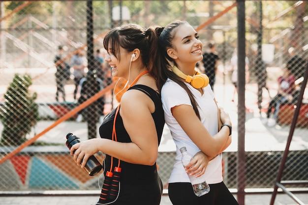 Zijaanzicht portret van twee mooie vriendin rusten en drinkwater na het doen van afvallen oefeningen in de ochtend buiten in een sportpark.