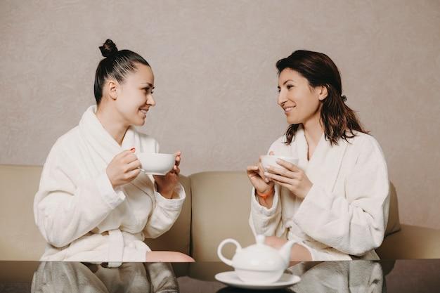 Zijaanzicht portret van twee mooie vrouw praten met een kopje thee in hun handen na spa-procedures gekleed in badjas in een wellness-spa-centrum.
