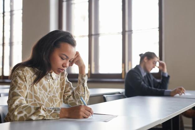Zijaanzicht portret van twee studenten die examen op rij afleggen terwijl ze aan een bureau zitten met sociale afstand, focus op jonge afro-amerikaanse vrouw op de voorgrond, kopieer ruimte
