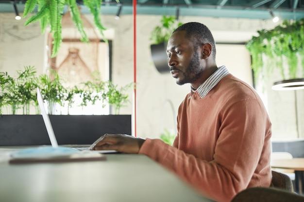 Zijaanzicht portret van volwassen afro-amerikaanse man met laptop in modern café-interieur versierd met verse groene planten, kopieer ruimte