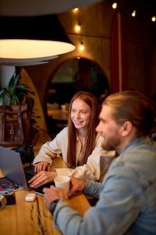 Zijaanzicht portret van vrolijke blanke managers fotografen roodharige vrouwelijke en bebaarde man die in café werkt, laptop gebruikt, op internet surft, praat, ruimte kopieert. freelance concept