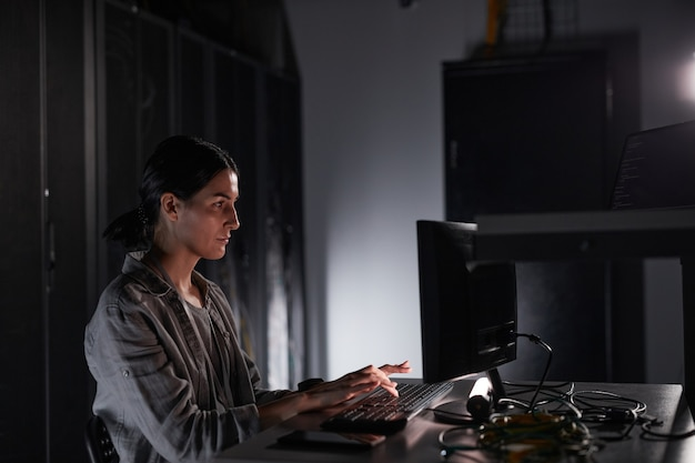 Zijaanzicht portret van vrouwelijke netwerkingenieur die laptop gebruikt terwijl ze in een donkere serverruimte zit, kopieer ruimte