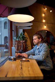 Zijaanzicht portret van zelfverzekerde blanke man in spijkerjasje bezig met laptop, gericht op werk, zijaanzicht portret. hipster man geniet van werken aan freelance, denken