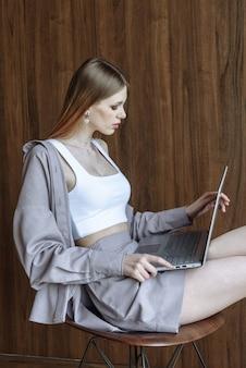 Zijaanzicht portret vrouw die aan laptop werkt terwijl ze zit