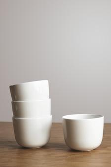 Zijaanzicht rechte gevormde lege witte eenvoudige koffiekopjes in pyramide op dikke houten tafel geïsoleerd