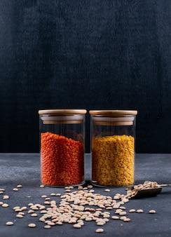 Zijaanzicht rode en gele linzen in glazen pot met ijzeren kruiden lepel op donkere steen en zwarte tafel