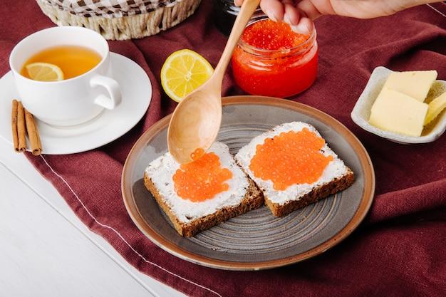 Zijaanzicht rode kaviaar toast roggebrood met cottage cheese rode kaviaar boter kopje thee en schijfje citroen op tafel