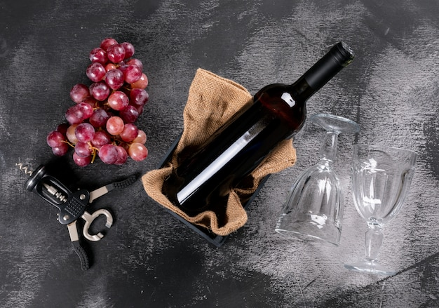 Zijaanzicht rode wijn met druif in krat met jute op zwarte horizontale steen