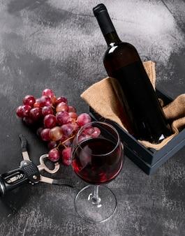 Zijaanzicht rode wijn met druif in krat met jute op zwarte steenverticaal