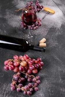 Zijaanzicht rode wijn met druif op zwarte steenverticaal