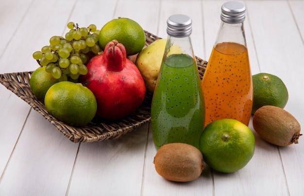 Zijaanzicht sapflessen met granaatappels, druiven, mandarijnen en peren in een mand op een witte muur
