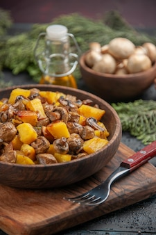 Zijaanzicht schotel olie en takken bruine kom aardappelen met champignons op de snijplank naast de vork onder olie kom witte champignons en vuren takken