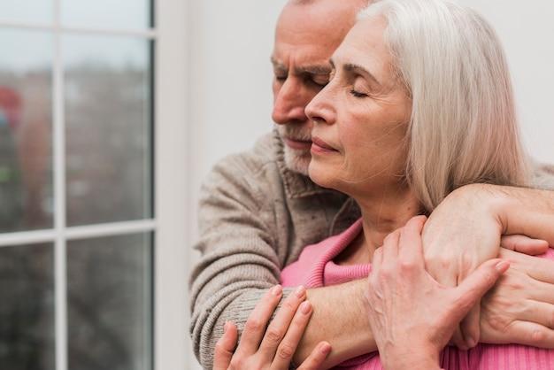 Zijaanzicht senior koppel knuffelen