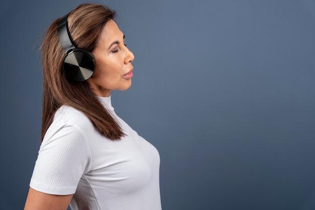 Zijaanzicht senior vrouw die naar muziek luistert via een koptelefoon