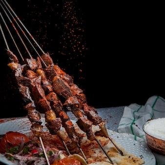Zijaanzicht shish kebab op spiesjes met tomaat en papier en ayran in witte plaat
