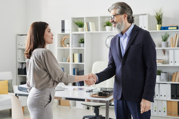 Zijaanzicht shot van moderne jonge vrouw die volwassen hr-manager begroet met handdruk voordat ze aan het sollicitatiegesprek begint