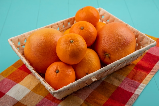 Zijaanzicht sinaasappelen met grapefruit in een mand op een geruite handdoek op een turkooizen achtergrond