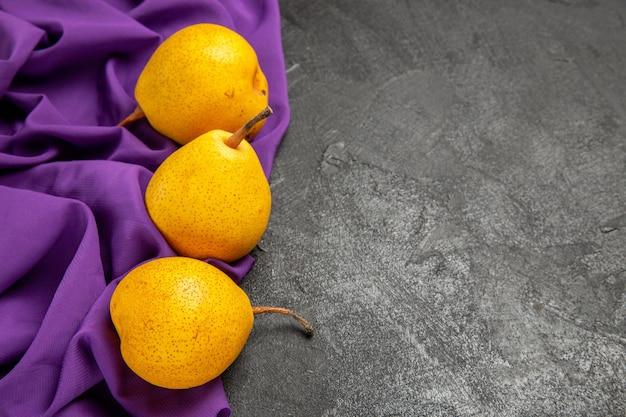 Zijaanzicht smakelijke peren smakelijke peren op het paarse tafelkleed aan de linkerkant van de tafel