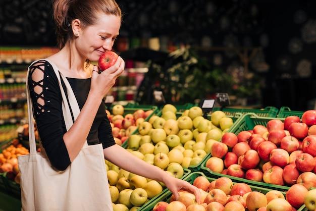 Zijaanzicht smiley vrouw ruiken een appel