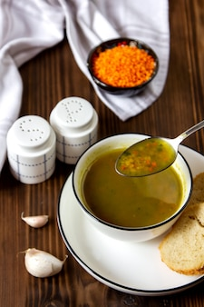Zijaanzicht soep met linzen met sneetjes brood met zout en peper