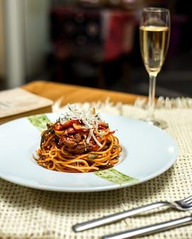 Zijaanzicht spaghetti met vlees en geraspte kaas en een glas champagne