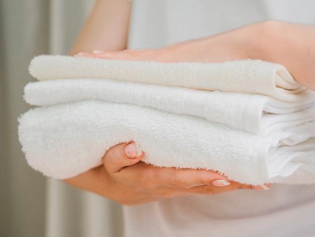 Zijaanzicht stapel handdoeken tussen handen