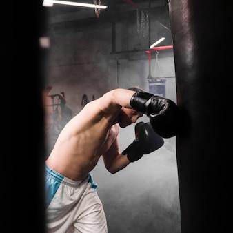 Zijaanzicht sterke mannelijke bokser training voor een wedstrijd