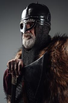 Zijaanzicht studio shot van geïsoleerde in grijze achtergrond oude man viking zwaaiende bijl.