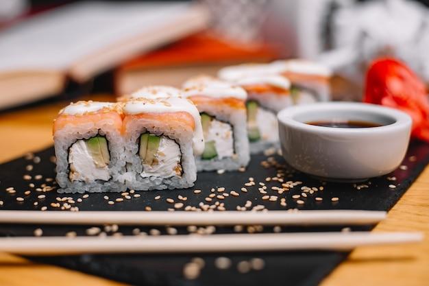 Zijaanzicht sushi philadelphia rolt in saus en sojasaus en sesamzaadjes op een standaard