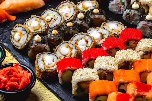 Zijaanzicht sushi set alaska roll chuckien hot roll california met krabvlees en tobiko kaviaar maki en philadelphia met roomkaas op een dienblad