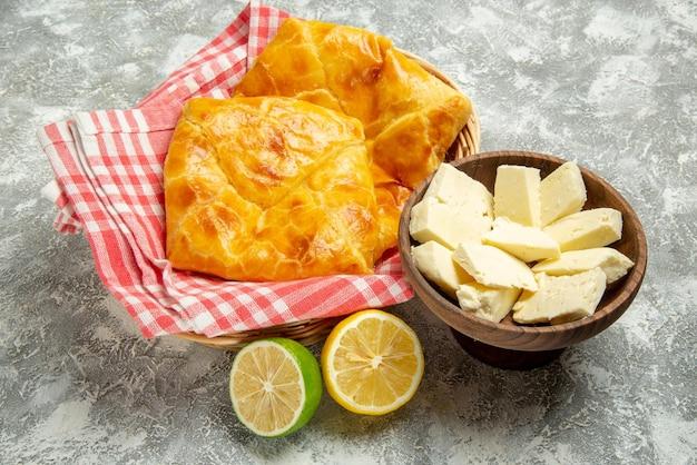 Zijaanzicht taarten en citroenen plaat van kaas, citroen en limoen naast de houten mand met smakelijke taarten en tafelkleed op de grijze achtergrond
