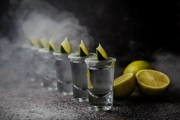 Zijaanzicht tequila in een glas geserveerd met limoenen en zout