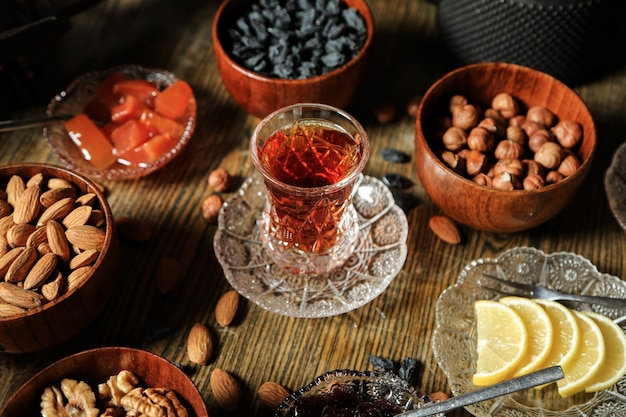 Zijaanzicht theestel rozijnen amandelen noten kweepeerjam met thee op tafel