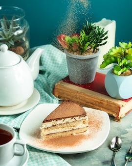 Zijaanzicht tiramisu dessert met een boek en een plant op tafel