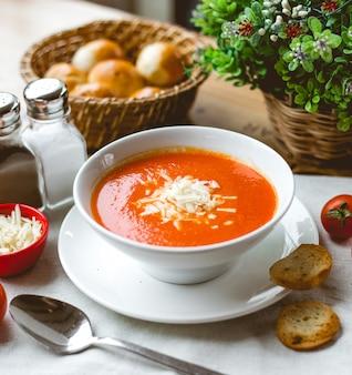 Zijaanzicht tomatensoep met geraspte kaas en crackers