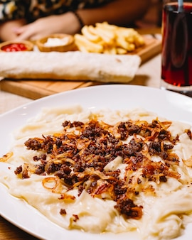 Zijaanzicht traditioneel azerbeidzjaans gerecht khinkali blad met gegrild gehakt