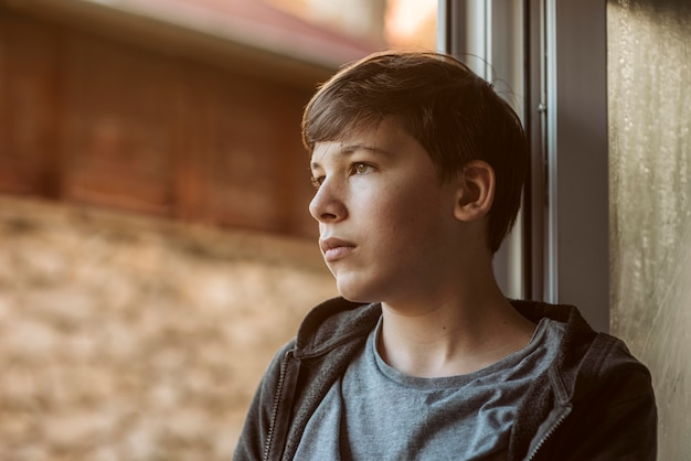Zijaanzicht trieste jongen naar buiten kijken