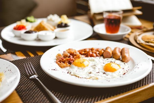 Zijaanzicht twee gebakken eieren met worstjes bonen en spek op een plaat