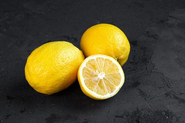 Zijaanzicht twee hele citroenen met een schijfje gehakte citroen