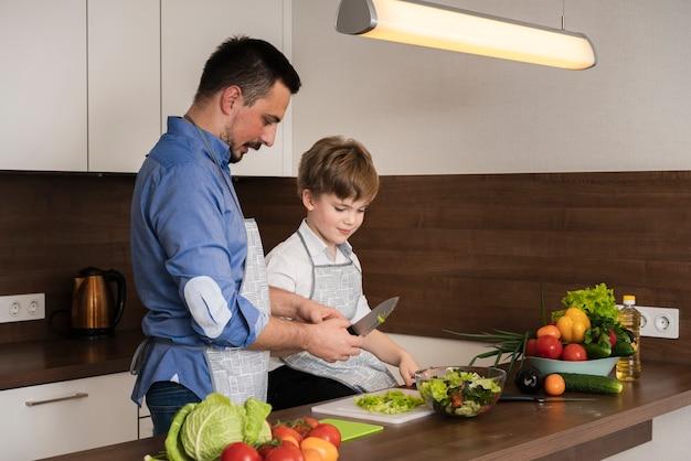 Zijaanzicht vader en zoon groenten snijden