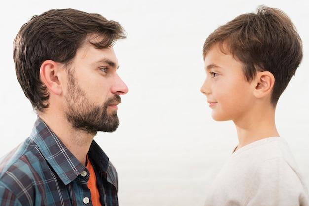 Zijaanzicht vader en zoon kijken elkaar aan