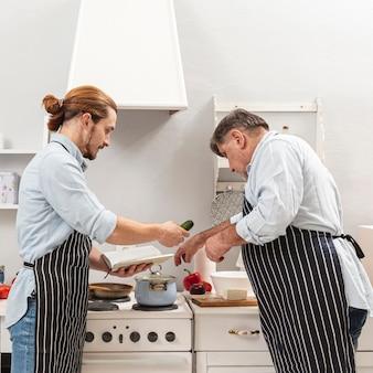Zijaanzicht vader en zoon samen koken