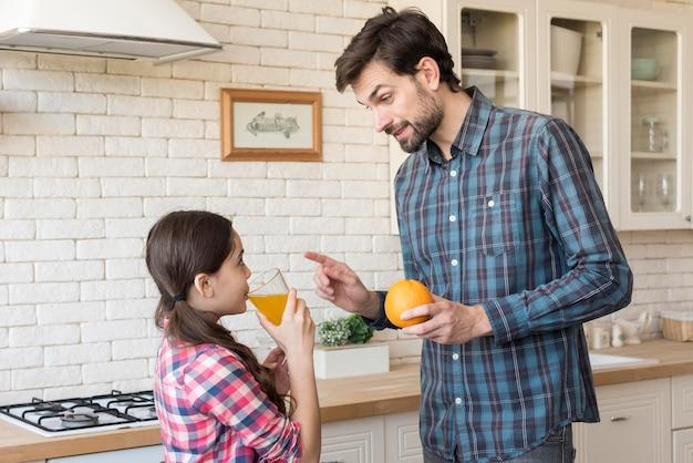 Zijaanzicht vader onderwijs meisje over vitamines