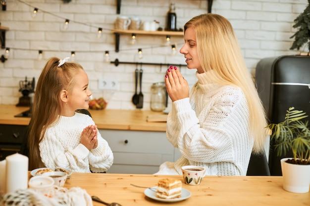 Zijaanzicht van aantrekkelijke jonge blanke vrouw in witte trui zegt genade voor het diner zittend aan de keukentafel met haar dochtertje, handen samen te drukken, gebak te eten en thee te drinken