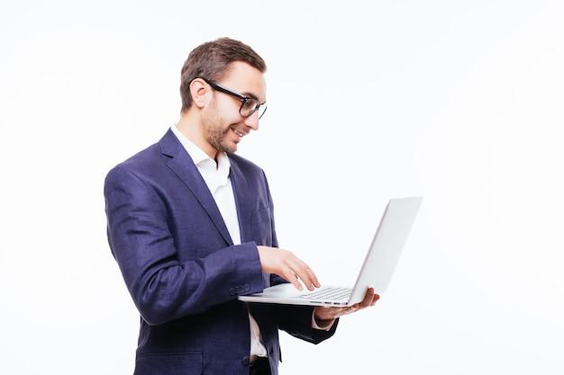 Zijaanzicht van aantrekkelijke jonge zakenman in klassiek pak met behulp van laptop, staande tegen een witte muur