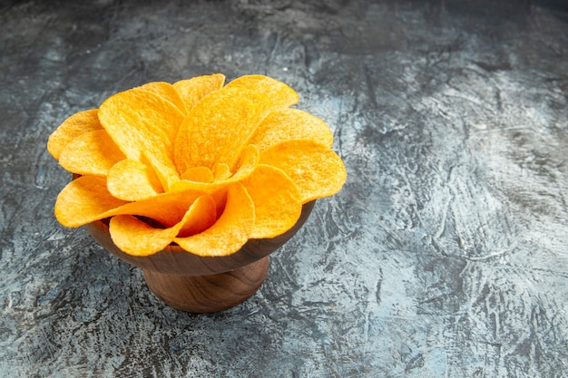 Zijaanzicht van aardappelchips versierd als bloem gevormd in een bruine kom op grijze tafel