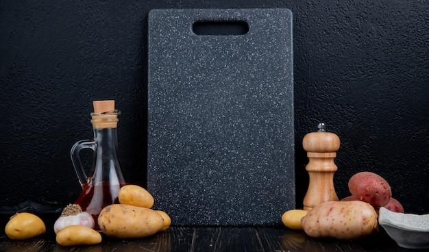 Zijaanzicht van aardappelen met gesmolten boter knoflook en snijplank op houten oppervlak en zwarte achtergrond