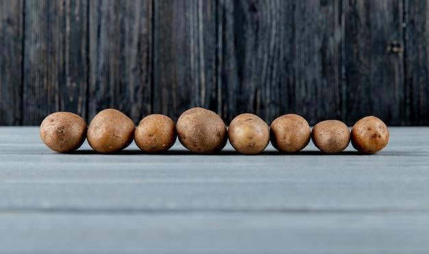 Zijaanzicht van aardappelen op houten oppervlak en achtergrond met kopie ruimte 3