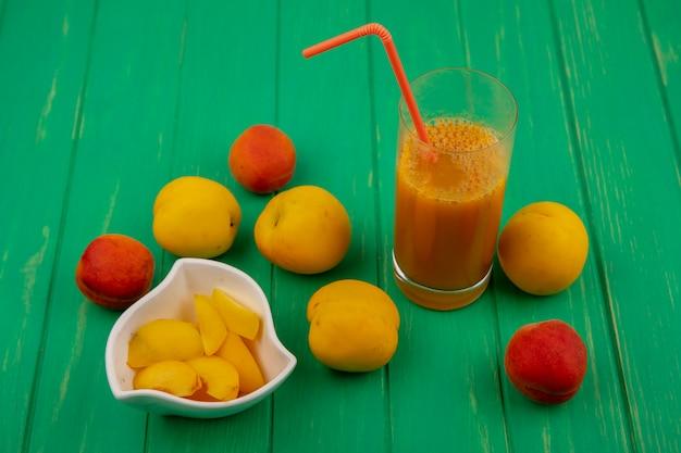 Zijaanzicht van abrikozenplakken in kom en abrikozensap met drinkbuis in glas en abrikozen rond op groene achtergrond